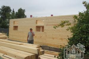 Складированный строительный материал на фоне строящегося дома