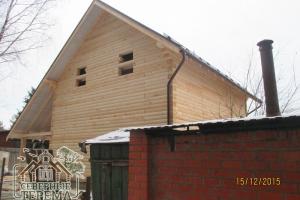 Вид на собранный в зимнее время дом с проезжей части