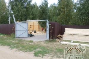 Складированные пиломатериалы за забором (справа)