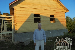 На фоне готового деревянного дома