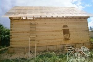 Собранная коробка дома из профилированного бруса, установлена стропильная система, обрешетка крыши