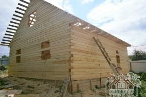 Вид с угла, фронтон и фасадная часть дома из бруса, установленного на ленточный монолитный фундамент