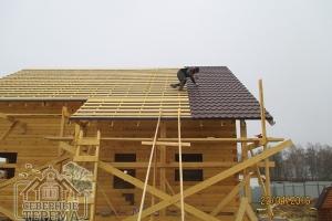 Бригада выполняет покрытие крыши дома из бруса металлочерепицей