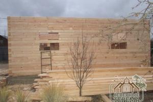 Стены дома из бруса ряд за рядом, параллельно собираются перегородки