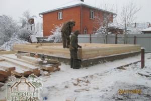 Установка деревянных нагелей в отверстия на углах сруба из бруса